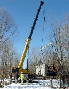 The 1918 historic Snyder Brook Pony Howe Truss Bridge was lifted from its cut stone abutments, the east partially broken apart, on Friday, Dec. 5 by operator John Lavoie of Littleton of CCS Crane Service of Morrisville, Vt., and then placed on a dirt platform on the north side of Presidential Recreational Rail Trail in Randolph. The dilapidated abutment and bridge will be repaired, and the bridge put back in place in summer 2015. Photo taken from east (Gorham) side of brook; crane is on west (Jefferson) side.