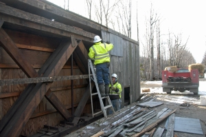 The interior siding was removed from the north side of the historic 1918 Snyder Brook rail bridge, revealing diagonal wood trusses and vertical bolts secured by (unseen) large nuts, on Tuesday, Dec. 2, as part of the preparations for Friday's lift by brothers Harlan and Vernon Crawford of Canaan, Vt., both crew members of Northern New England Field Services, LLC, of Stewartstown, owned by Dennis Thompson who provided on-site direction throughout the project.